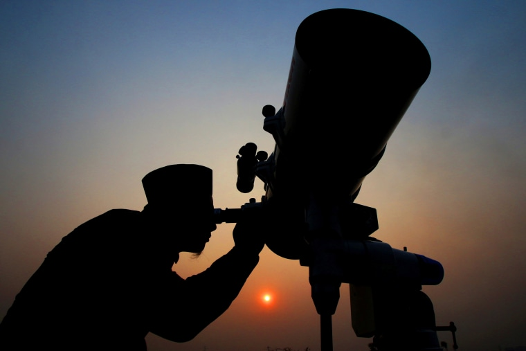 Image: An official looks through a telescope for the sighting of the new moon for the start of the Muslim fasting month of Ramadan at a religious boarding school in Jakarta