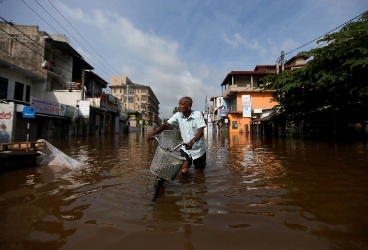 Image: A man pushes his bike through a flooded road in Nagoda village, in Kalutara