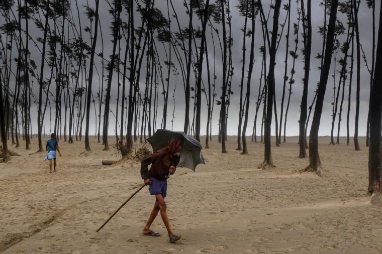 Image: A Bangladeshi villager evacuates to a cyclone shelter