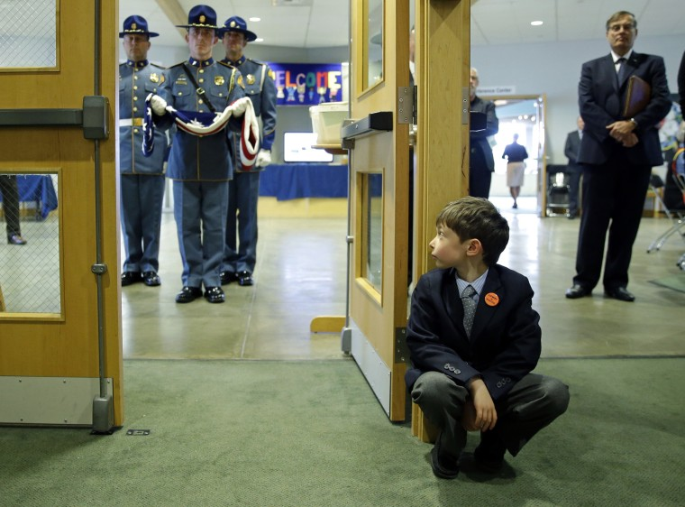 Image: A grandson of former Washington Gov. Mike Lowry watches as an honor guard holds a U.S. flag