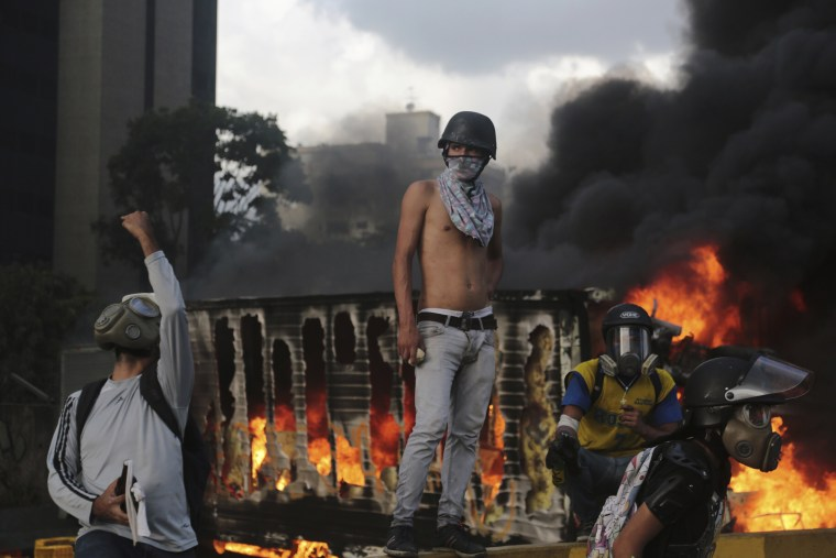 Image: Protesters eye security forces after seizing and lighting a truck on fire during clashes in Caracas