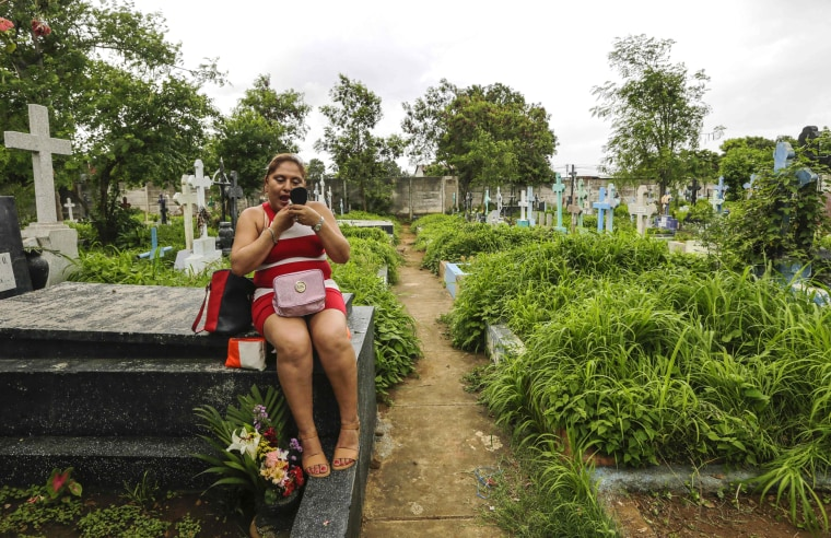 Image: A woman puts on makeup while sitting on her mother's tomb at the Central Cemetery in Managua