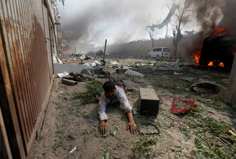 Image: A wounded man lies on the ground at the site of a blast in Kabul, Afghanistan