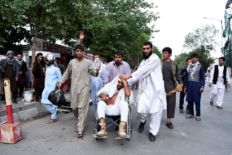 Image: Afghan relatives push the wheelchair of a wounded man outside an Italian aid organization's hospital following the series of explosions.