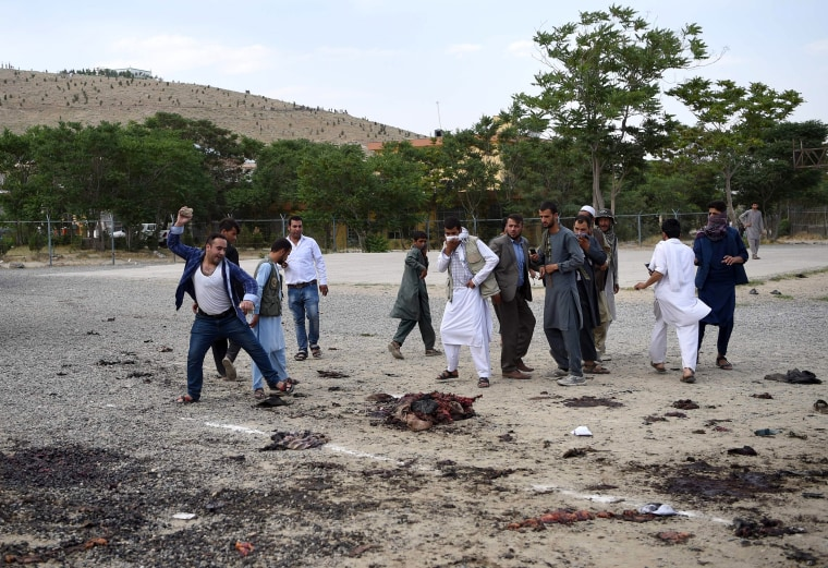 Image: An angry Afghan man throws a rock at what was thought to be the remains of one of the attackers.