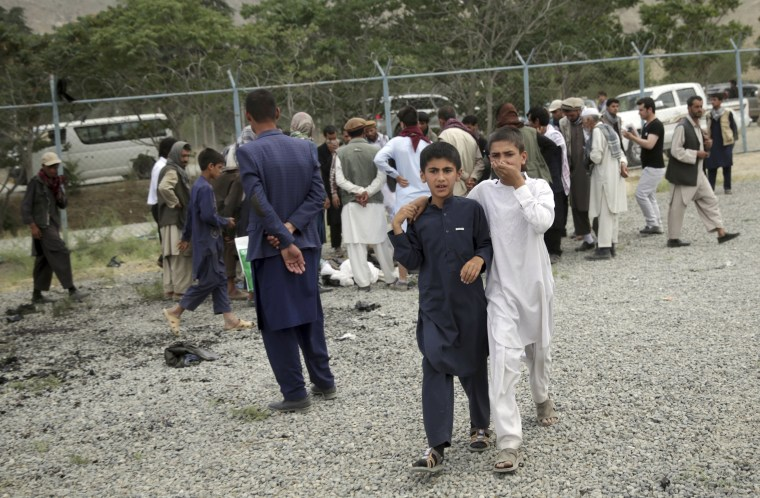 Image: Boys walk away from the site of the three suicide attacks.