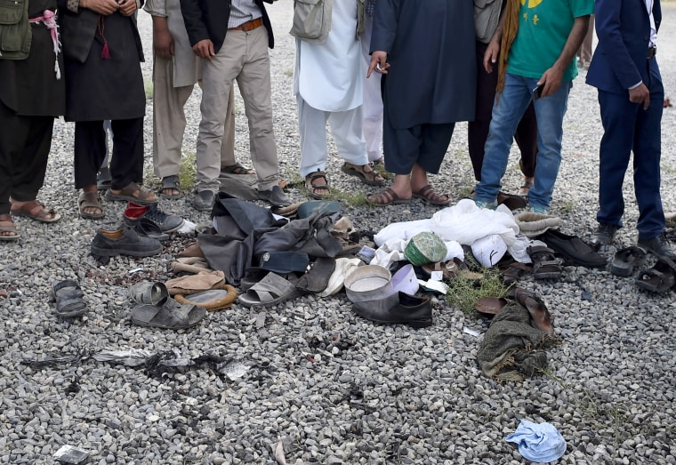 Image: Men look over the belongings of blast victims.