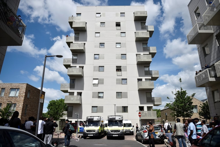 Image: Officers and vehicles stand outside a block of flats that was raided by police in Barking, east London