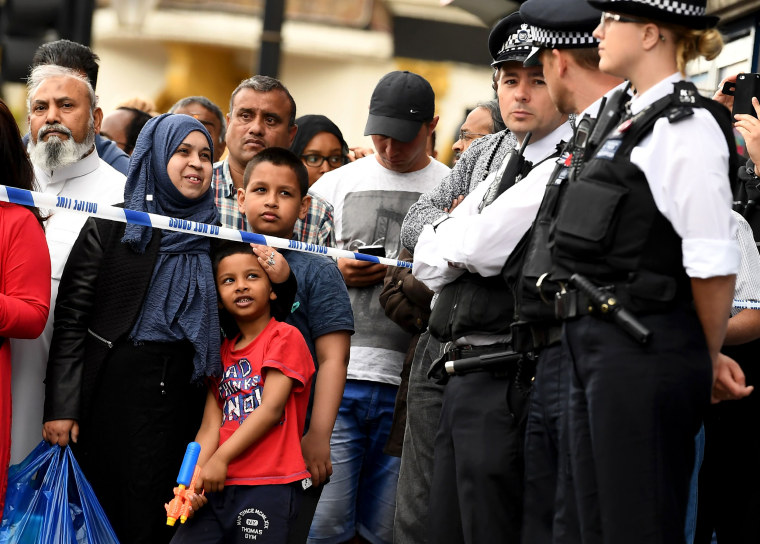 Image: A boy holds a water gun as police officers stand on duty inside a cordon in East Ham,where police are conducting a raid.