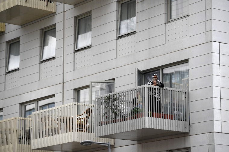 Image: A woman films the scene on her phone from a balcony overlooking a block of flats which was raided by police in connection with last night's terrorist attack, in Barking, England. Police have arrested 12 people after raids in Barking.