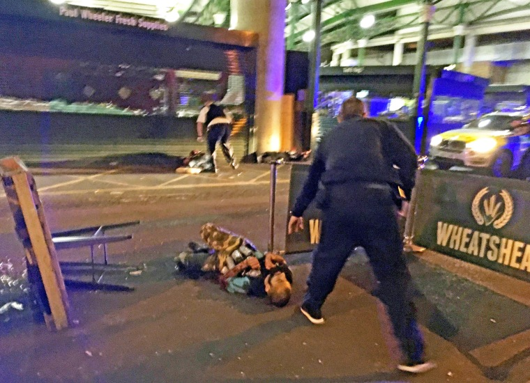 Image: A suspected terrorist, wearing what appear to be canisters around his waist, is on the ground after being knocked down by police officers in Borough Market, late last night. He was shot and killed by police officers.