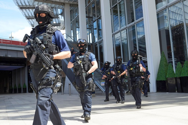 Image: Armed police officers patrol outside The Shard tower and London Bridge railway station.