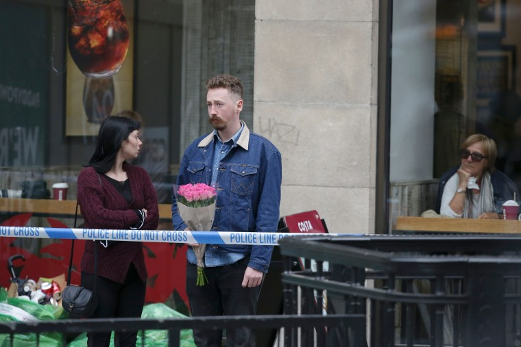 Image: A couple leave a bunch of flowers at the police cordon at the north end of the London Bridge.