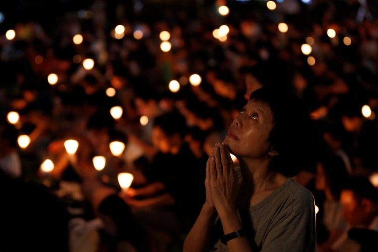 Image: A woman reacts during a candlelight vigil to mark the 28th anniversary of the crackdown of the pro-democracy movement at Beijing's Tiananmen Square in 1989, at Victoria Park in Hong Kong