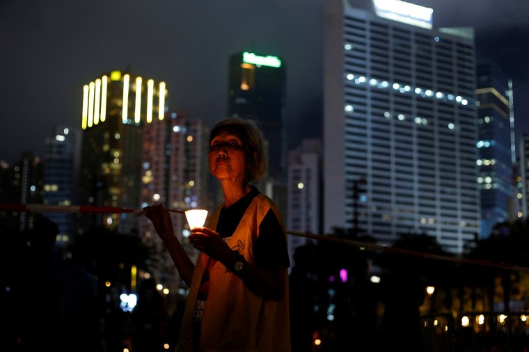 Image: A woman takes part in a candlelight vigil to mark the 28th anniversary of the crackdown of the pro-democracy movement at Beijing's Tiananmen Square in 1989, at Victoria Park in Hong Kong