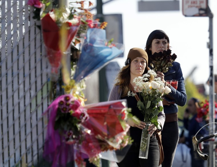 Image: Well-wishers walk to place flowers at the scene in the aftermath of a warehouse fire