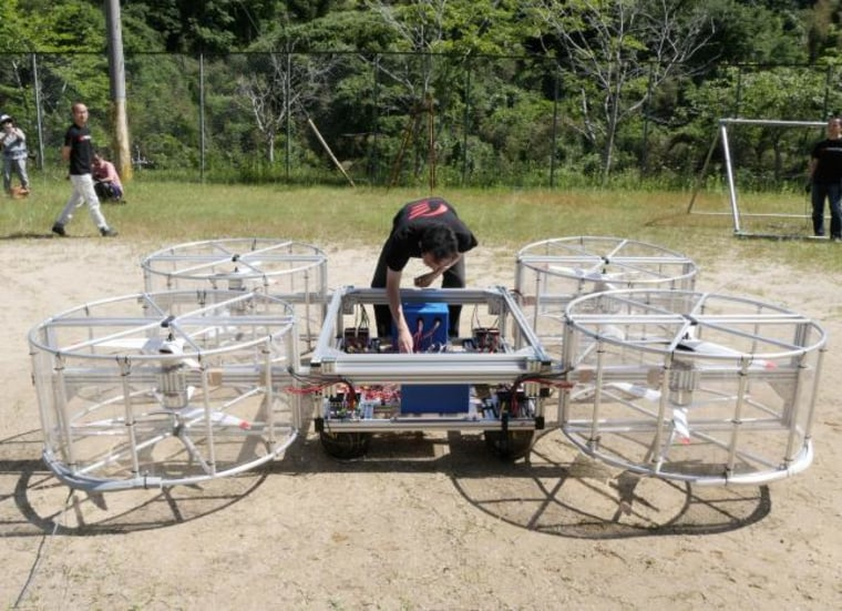 A staff member of Cartivator checks their flying car during a demonstration in Toyota