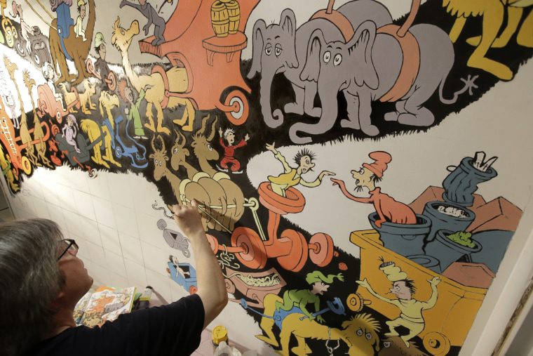 Image: John Simpson, project director of exhibitions for The Amazing World of Dr. Seuss Museum, paints a mural