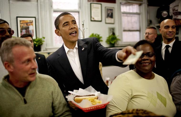 Image: U.S. President-elect Barack Obama, center, pays for a chili