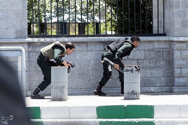 Image: Members of Iranian forces take cover during an attack on the Iranian parliament in central Tehran