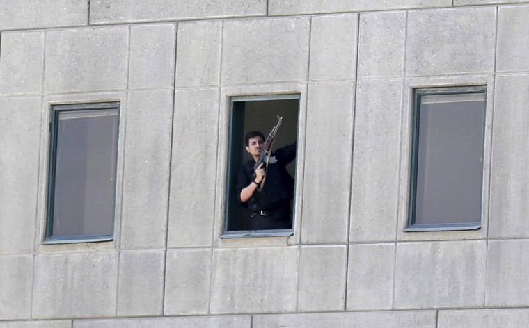 Image: An armed man stands in a window of the parliament building in Tehran