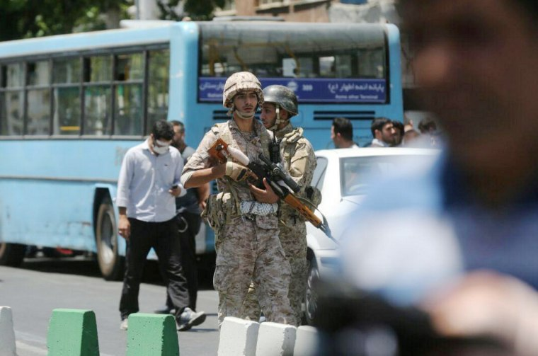 Image: Members of Iranian forces stand guard during an attack on the Iranian parliament in central Tehran