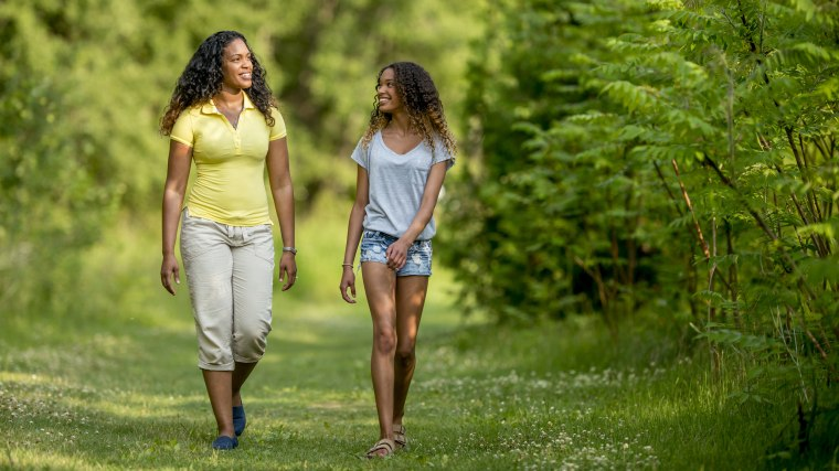 Image: A mother and daughter are walking on a grassy path through a park
