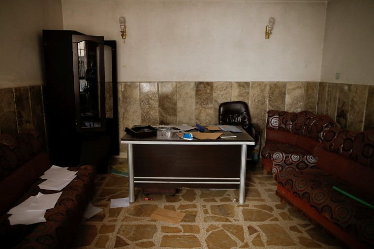 Image: Documents and envelopes are scattered inside an office, at a compound used as a prison by Islamic State militants