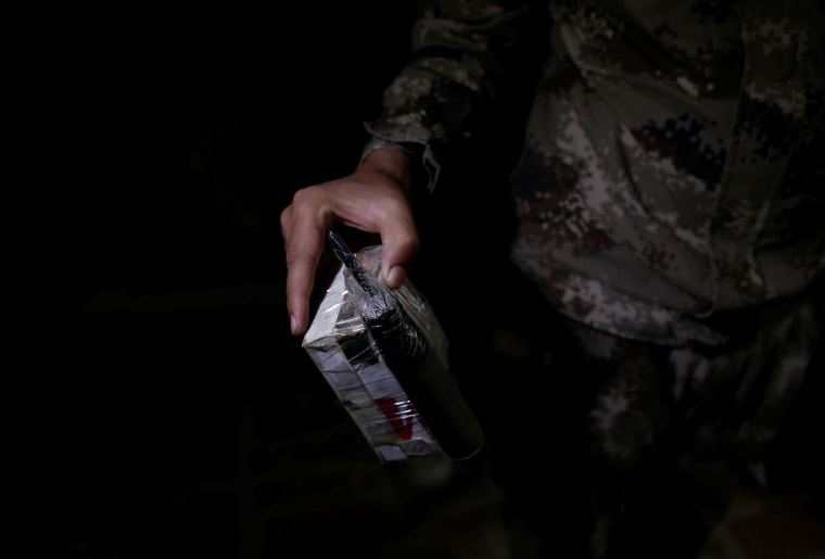Image: A member of the Iraqi Army's 9th Armoured Division holds a self-made bomb found inside a compound used as a prison by Islamic State militants