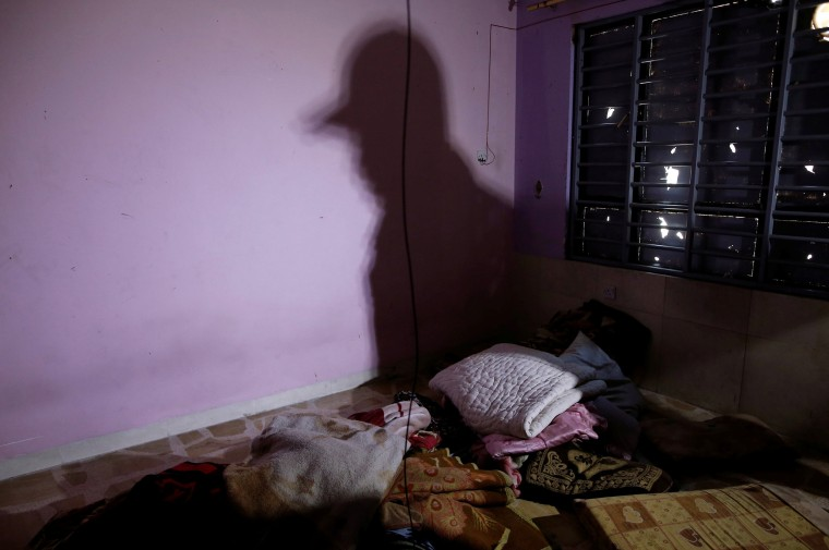 Image: The shadow of a member of the Iraqi Army's 9th Armoured Division is seen in a room used as a cell for men, inside a compound used as a prison by Islamic State militants
