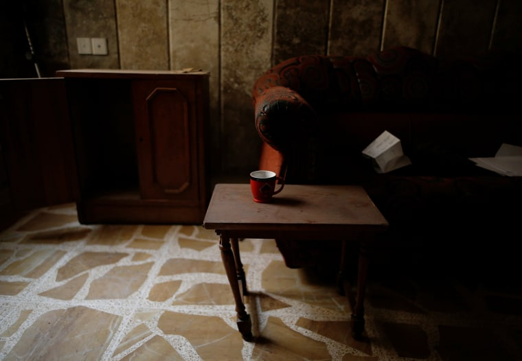 Image: A coffee mug is seen on a table at a compound used as a prison by Islamic State militants