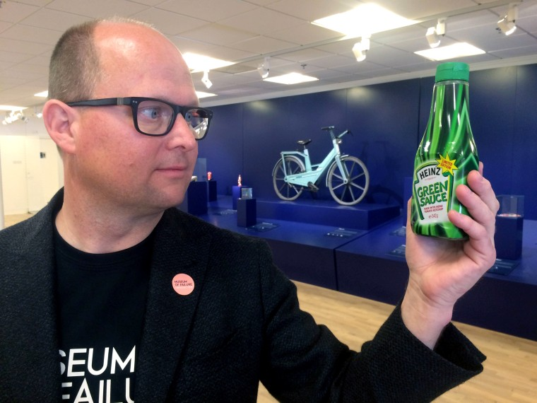 """Image: Samuel West, curator of the Museum of Failure, holds a bottle of Heinz's """"Green Sauce"""""""