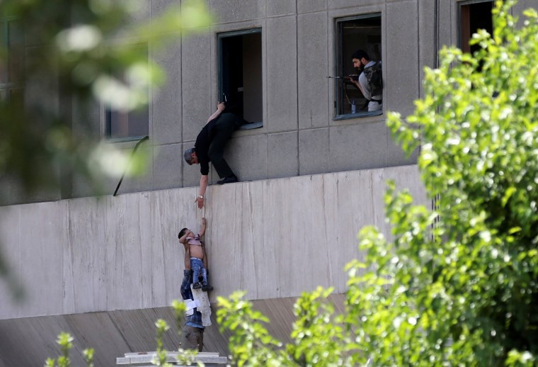 Image: Boy is evacuated during an attack on the Iranian parliament in central Tehran