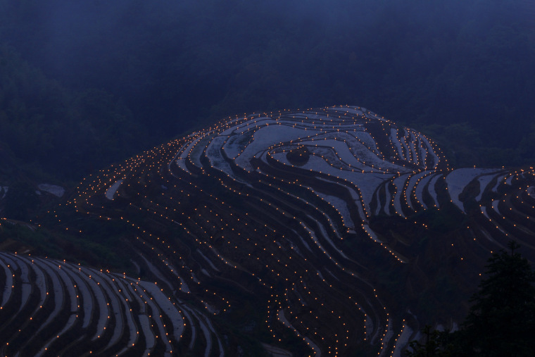 Image: Thousands of torches are placed in terraced fields by villagers during a local festival praying for good harvest at Guilin