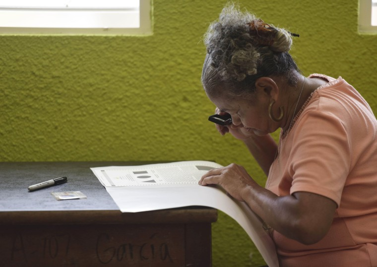 Image: Puerto Rican resident Marla Quinones looks carefully at her ballot