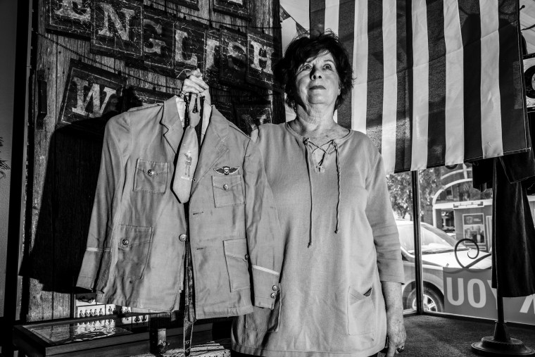 Image: Donna Selk, of Anamosa, holds the uniform her husband wore as a child as she talks about how she thinks Trump's presidency is going so far.