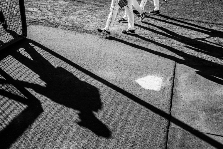Image: Shadows cast by members of a Cedar Rapids minor league baseball team named the Kernals as they play a game.