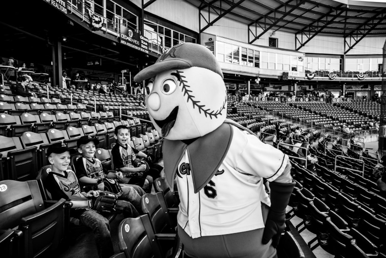 Image: Members of a Cedar Rapids minor league baseball team named the Kernals laugh with a game mascot.