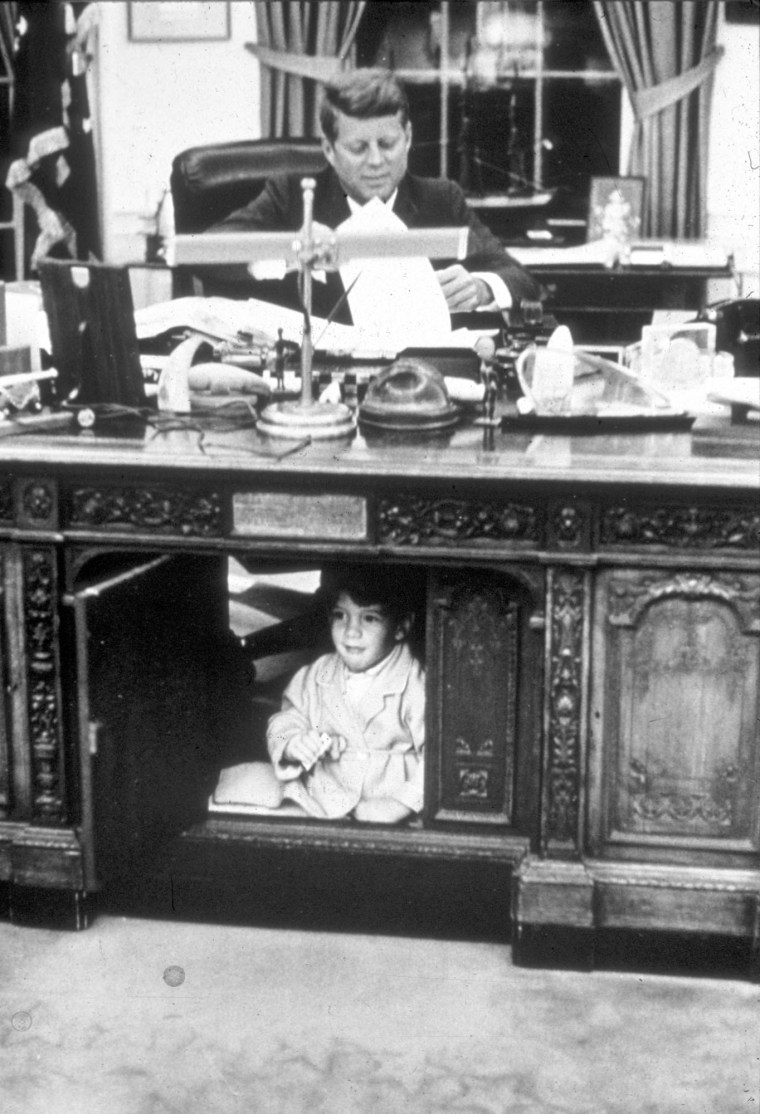 John F. Kennedy Jr. hides in his father's Oval Office desk in October, 1963.