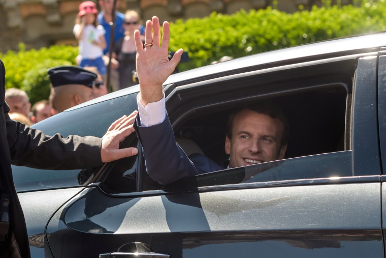 Image: French President Emmanuel Macron waves from his car after voting in parliamentary elections