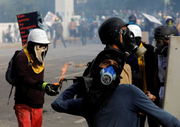 Image: A demonstrator throws a petrol bomb while clashing with riot security forces during a rally against Venezuela's President Nicolas Maduro in Caracas