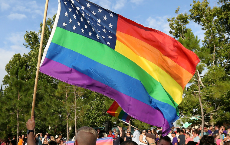 Image: FILE PHOTO - A rainbow U.S. flag is held up during a vigil for the Pulse night club victims in Orlando