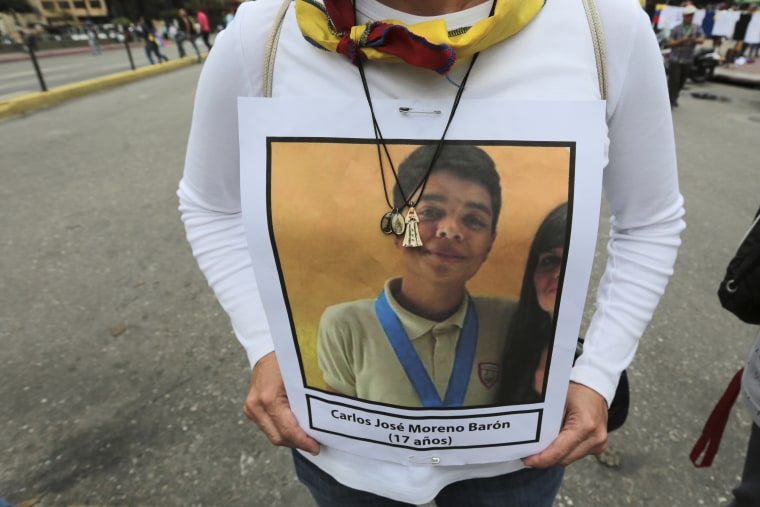 A woman carries a portrait of a person who died in past protests during a march towards the Ombudsman's Office in protest of President Nicolas Maduro in Caracas, Venezuela, Monday, May 29, 2017.
