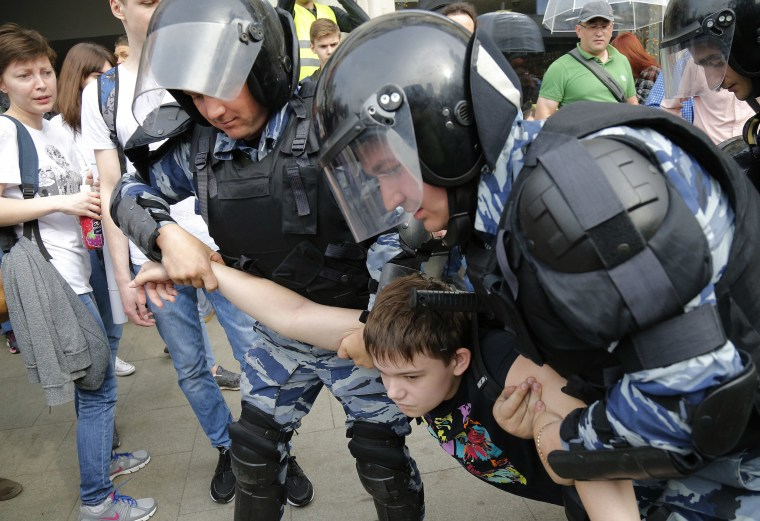 Image: A young demonstrator is apprehended by riot police during a demonstration in downtown Moscow