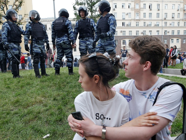 Image: A couple sits in front of riot police standing guard during an anti-corruption protest in central Moscow