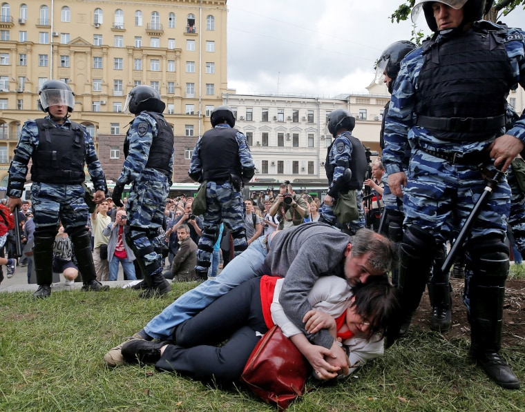Image: Activist Galyamina and her husband Tuzhilin lie on the ground next to riot police during an anti-corruption protest in central Moscow