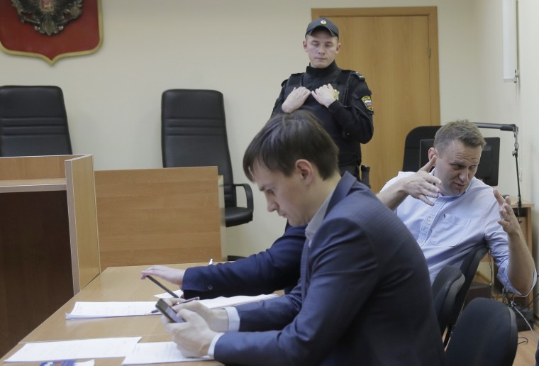 Image: Russian opposition leader Alexei Navalny, center, speaks before hearing in a court in Moscow