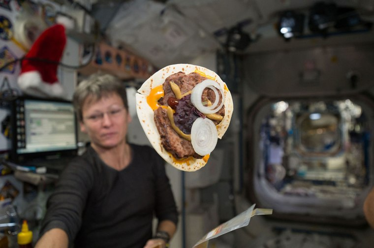 "A ""space cheeseburger,"" made using a tortilla for bread, is seen on board the International Space Station in late 2016. NASA astronaut Peggy Whitson floats in the background."