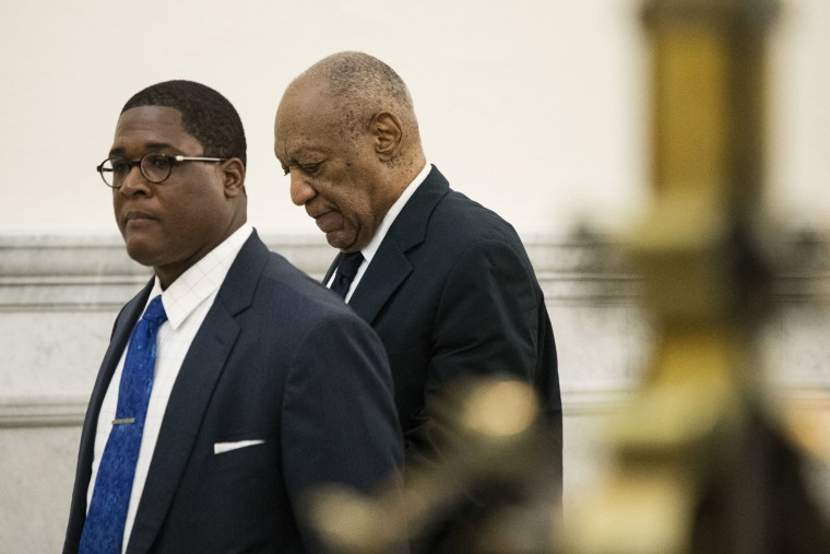 Image: Bill Cosby, accompanied by Andrew Wyatt, walks to the courtroom during jury deliberations