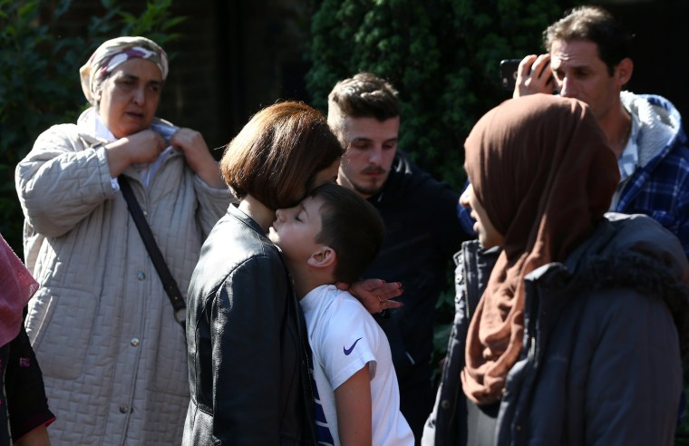 Image: A woman comforts a boy after a tower block was severly damaged by a serious fire in West London